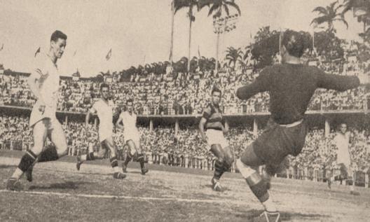 Fla x Flu nas Laranjeiras. O goleiro Jurandyr defende com os pés um chute frontal, enquanto Biguá permanece isolado e cercado entre vários jogadores do Fluminense. Crédito: revista Esporte Ilustrado.